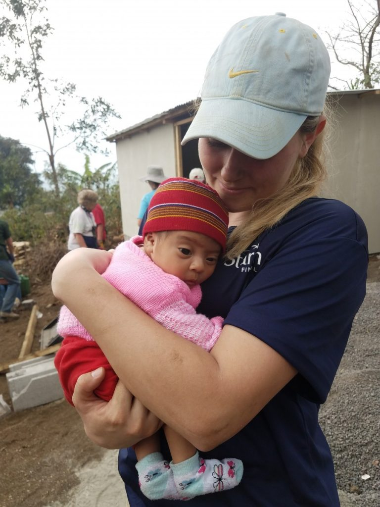 Hawley's Hannah Tollefsrud holding baby during a house build in rural Alotenengo, Guatemala.